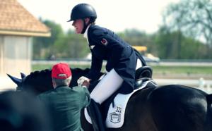 Lächelnde Frau sitzt mit Ihrem Markenreithelm auf einem Pferd